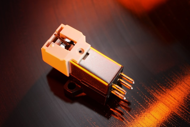 Magnetische grammofooncassette op vinylplatengroef. macrofoto.