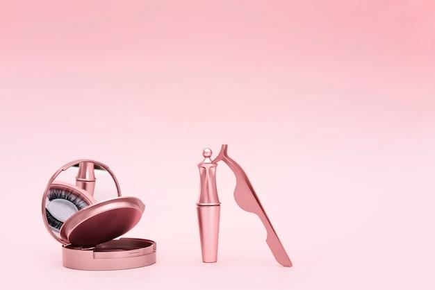 Magnetische nepwimper in spiegelkit, eyeliner, pincet geïsoleerd op roze