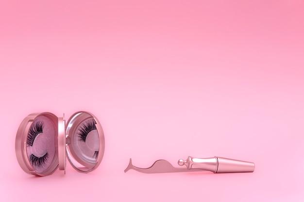 Magnetische nepwimpers in roze spiegelkit, eyeliner, pincet geïsoleerd op roze