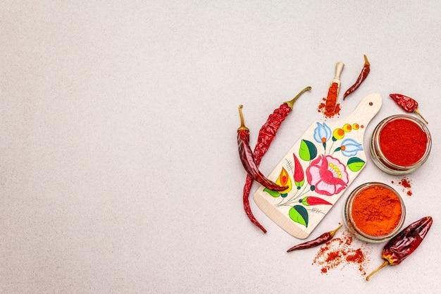 Magyar (hongaars) rood zoet en heet paprikapoeder. traditioneel patroon op een snijplank, verschillende soorten droge peper.