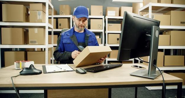 Mailman in uniform werken op de computer in de postkantoor winkel met pakketten.