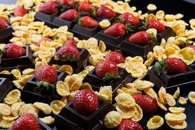 Maïs aardbei dessert in chocolade tegen een donkere achtergrond
