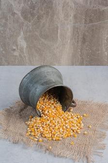 Maïs die uit een kleine metalen kan vloeit, is omgevallen op een stuk stof op een marmeren oppervlak