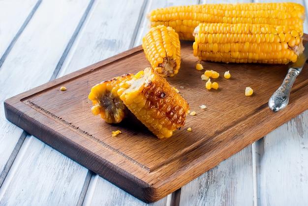 Maïs gegrild op een houten keuken bord met zout