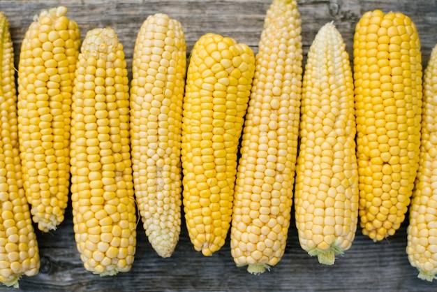 Maïs op de oude houten, biologische voedingswinkel, verse zoete gele maïs, landbouwproducten voor menselijke consumptie