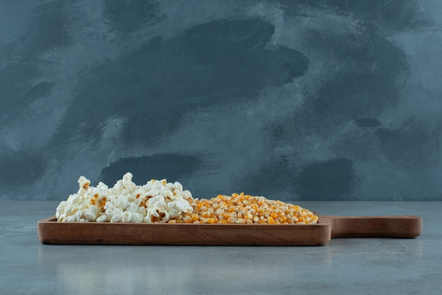 Maïs plant zaden en popcorns op blauwe achtergrond. hoge kwaliteit foto
