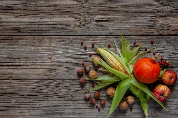 Maïs, pompoen, appels en noten op een vintage houten achtergrond.