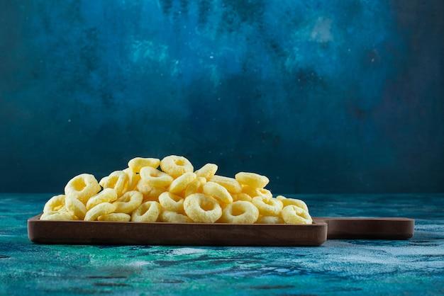 Maïs ringen in een bord op het blauwe oppervlak