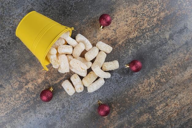 Maïs snacks gieten uit een emmer naast kerstballen op marmeren oppervlak