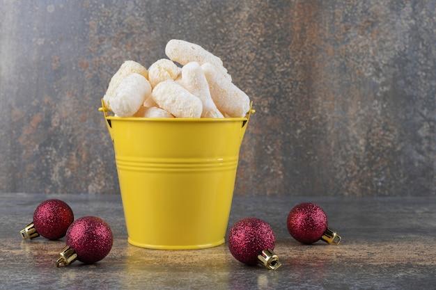 Maïs snacks opgestapeld in een emmer naast kerstballen op marmeren oppervlak
