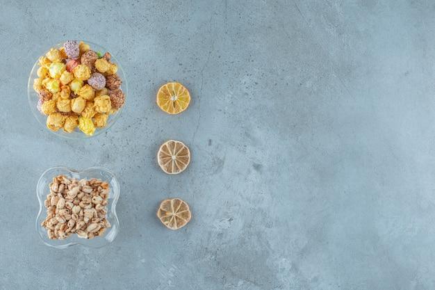 Maïsballen in een glas en cornflakes in een melkkoffieglas, op de blauwe achtergrond.