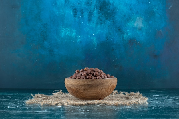 Maïsballen in een kom op een handdoek, op de blauwe tafel.