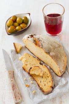 Maisbrood met olijven en rode wijn op papier