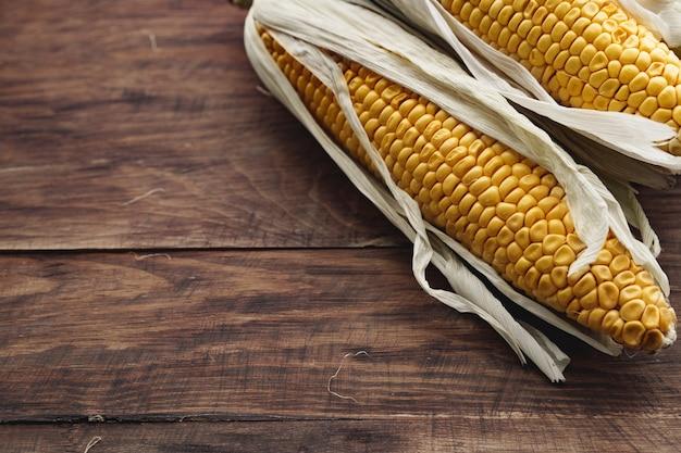Maïskolven op donkerbruine houten tafel