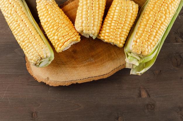 Maïskolven op een houten stuk op een houten lijst. plat lag.