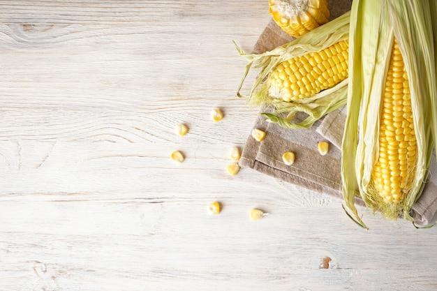 Maïskolven van rijpe rauwe maïs op witte houten achtergrond, ruimte voor tekst. plat leggen.
