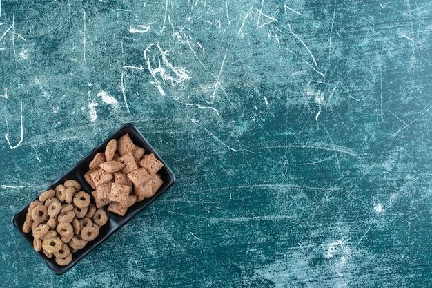 Maïspads en maïsringen in een kom, op de blauwe tafel.