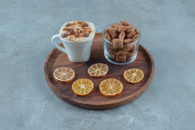 Maïspads op een glas naast schijfjes citroen en een kopje cappuccino op een houten bord, op de blauwe achtergrond. hoge kwaliteit foto