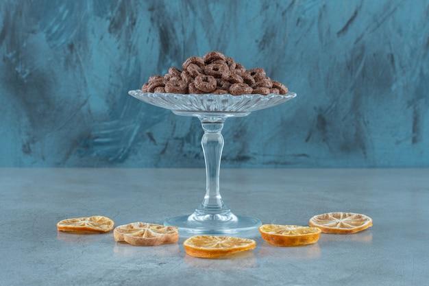 Maïsring op een glazen voetstuk naast schijfjes citroen, op de blauwe tafel.