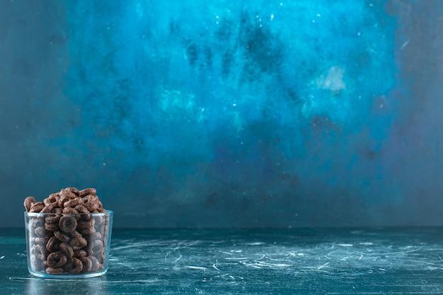 Maïsringen in een glazen kom, op de blauwe achtergrond. hoge kwaliteit foto