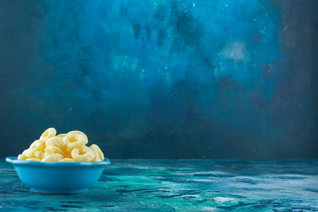 Maïsringen in een kom, op de blauwe tafel.