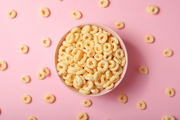 Maisringen in glazuur voor het ontbijt op een gekleurde achtergrond