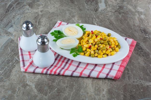 Maïssalade en gesneden ei op plaat naast zout op theedoek op marmer.