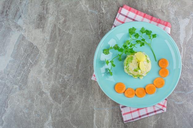 Maïssalade en gesneden wortelen op plaat op theedoek op marmer.