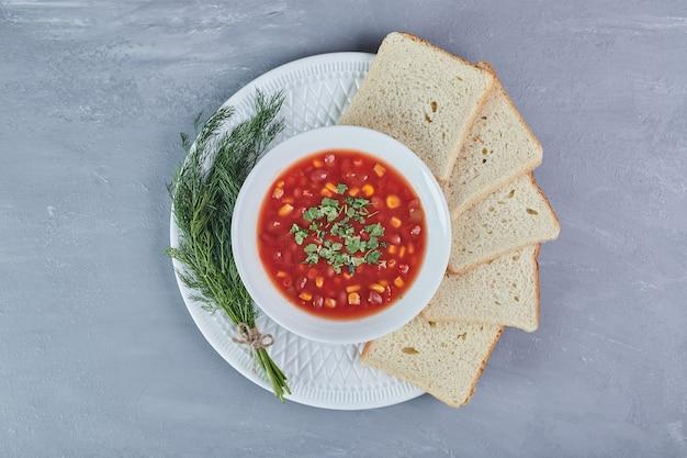 Maïssoep in tomatensaus in een wit bord met kruiden.