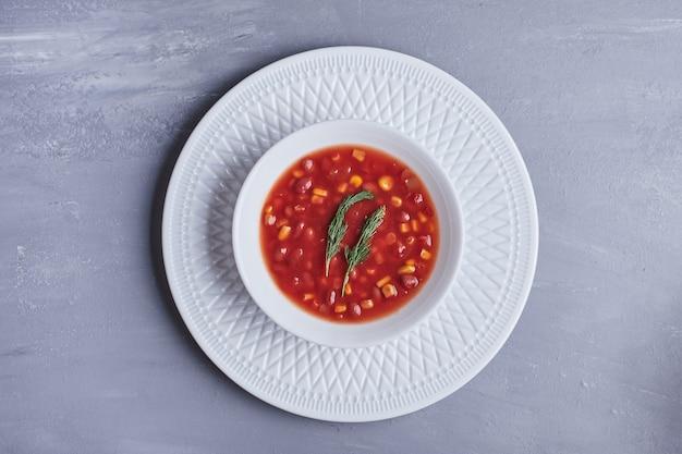 Maïssoep in tomatensaus in een witte kom.