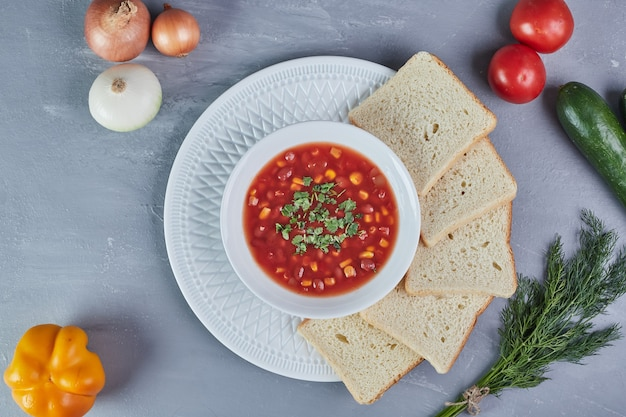Maissoep in tomatensaus met een bosje dille.