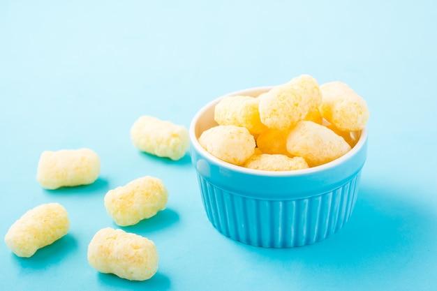 Maïsstokken in poedersuiker in een kom op een blauwe tafel. kinderen behandelen