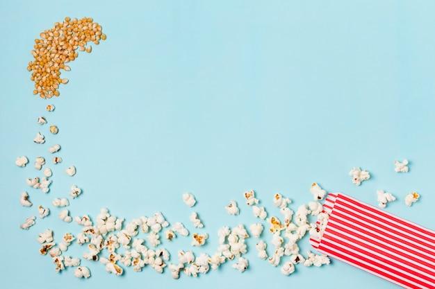 Maïszaadjes veranderen in popcorns die binnenkomen in de popcorndoos tegen een blauwe achtergrond