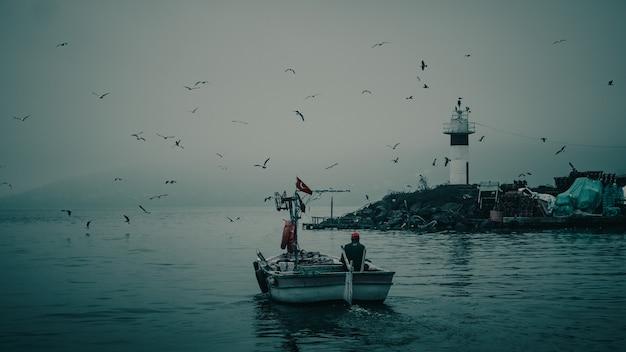 Majestueus achteraanzicht van een visser in een boot die vaart met een geweldig natuurtafereel