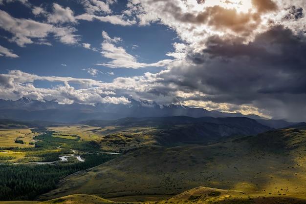 Majestueus panorama van de bergvlakte op de tafel van de met sneeuw bedekte bergkam voor onweer. zonnestralen breken door enorme wolken en verlichten prachtig de groene steppe en kronkelende rivier.