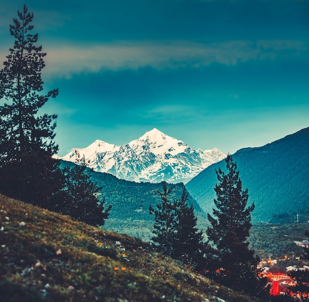 Majestueus uitzicht vanaf de groene vallei naar de machtige besneeuwde bergen van de kaukasus in georgië. prachtig sereen landschap. aantrekkelijke toeristische plek om te rusten en te ontspannen.