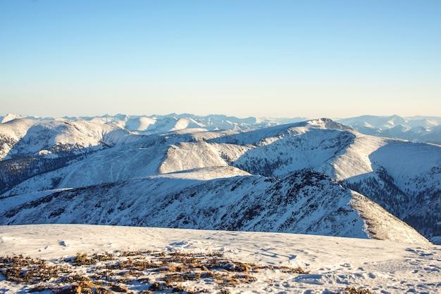 Majestueus winterlandschap van besneeuwde bergen met heldere blauwe hemel