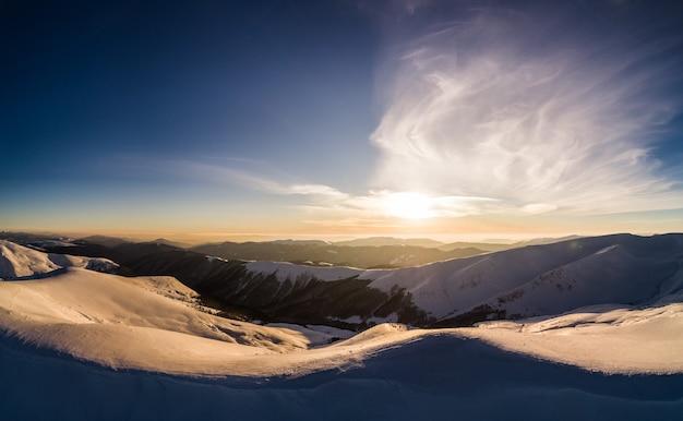 Majestueuze besneeuwde heuvels gelegen in de bergen op een zonnige winterdag met blauwe lucht in een skigebied in europa