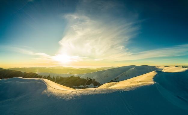 Majestueuze besneeuwde heuvels gelegen in de bergen op een zonnige winterdag met blauwe lucht in een skigebied