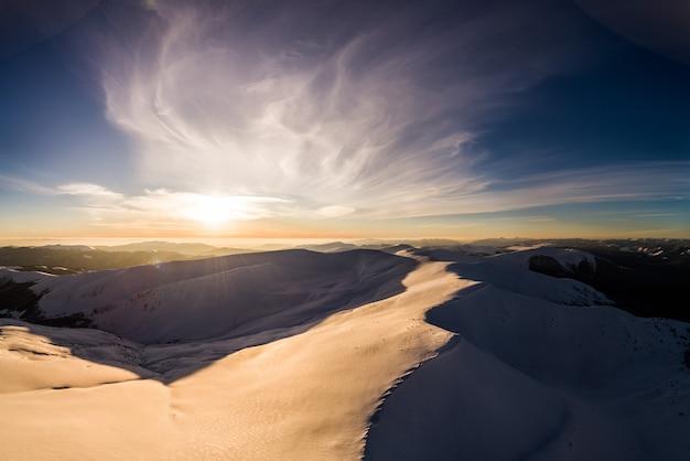 Majestueuze besneeuwde heuvels gelegen in de bergen op een zonnige winterdag met blauwe lucht in een skiresort