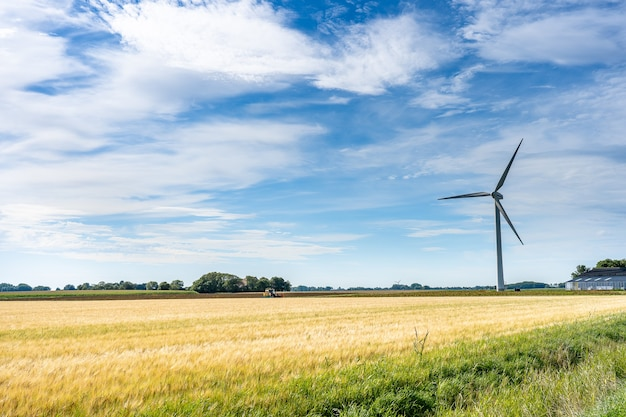 Majestueuze landschapsmening van land met een windmolen voor het opwekken van elektriciteit onder een bewolkte hemel
