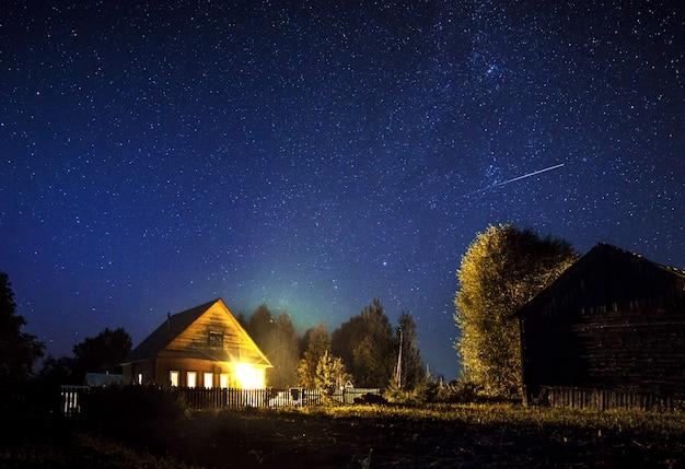 Majestueuze melkweg en de vallende ster boven het dorpshuis in de zomer. een sterrenhemel.