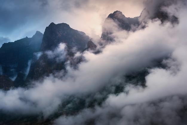 Majestueuze scène met bergen in wolken in donkere avond