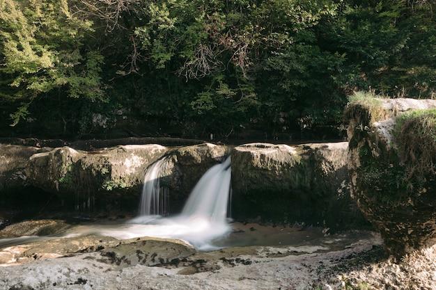 Majestueuze waterval in het bos. uitzicht op de waterval van de rivier van de berg