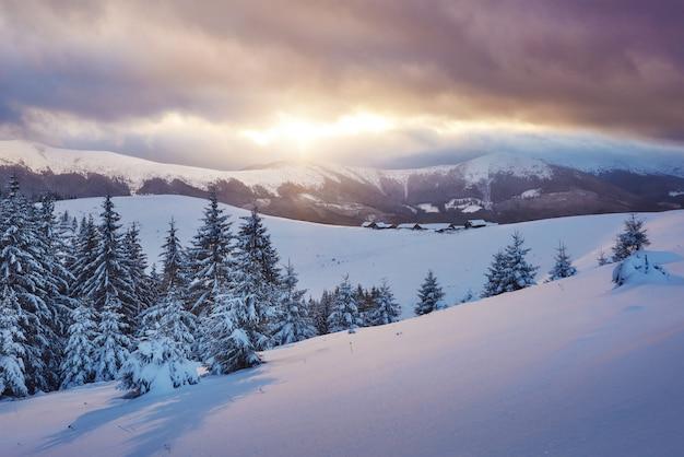 Majestueuze zonsondergang bij klein dorp op een sneeuwheuvel onder oekraïener