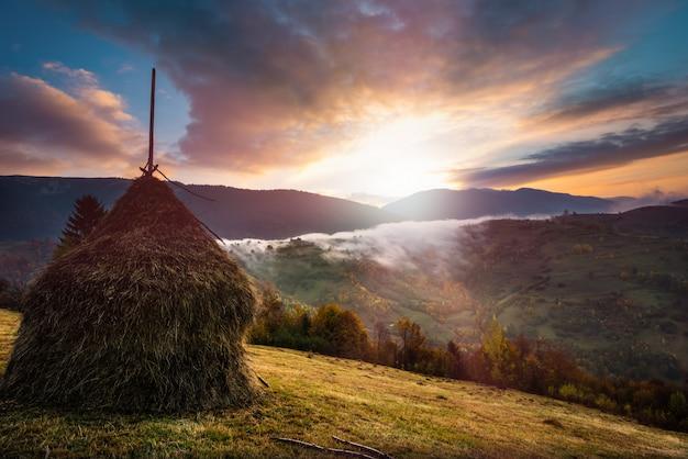 Majestueuze zonsopgang in mistige ochtend vallei met hooiberg op grasland heuvel