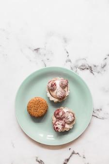 Makaron en twee kopcakes op plaat over de marmeren achtergrond