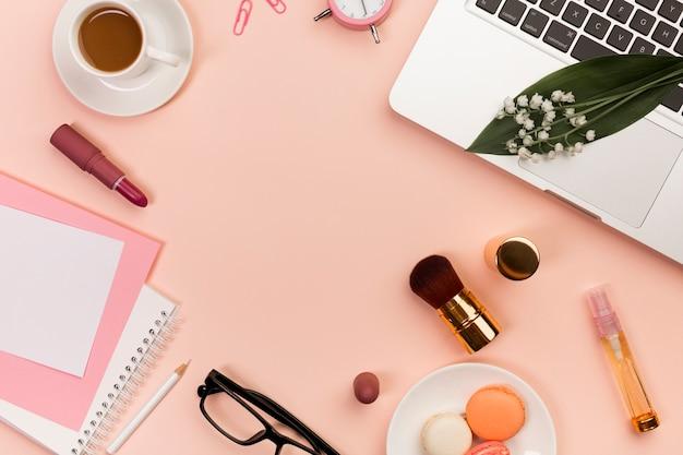 Makarons, make-upproducten, spiraalvormige blocnotes, koffiekop en laptop op perzik gekleurde achtergrond