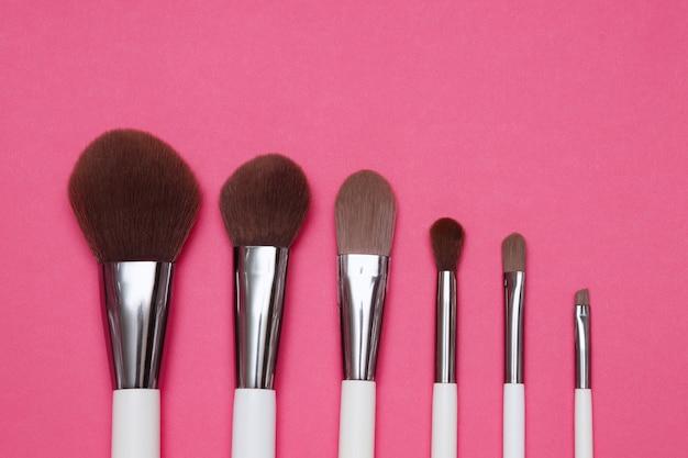 Make-up artiest borstels op een roze achtergrond. witte borstels