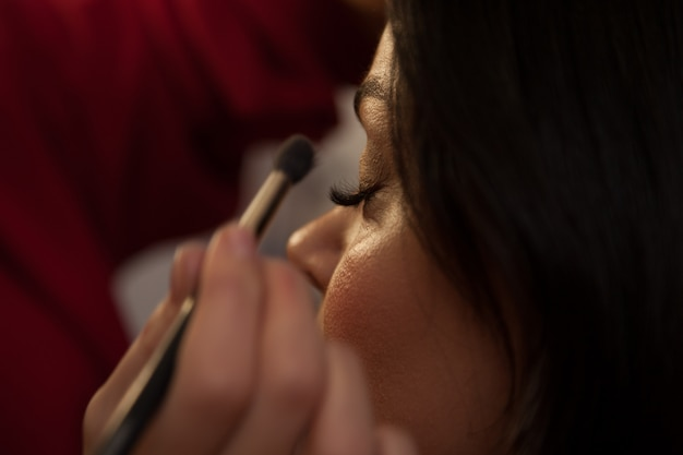 Make-up artiest doet make-up model. afro-amerikaanse modellen passen make-up toe